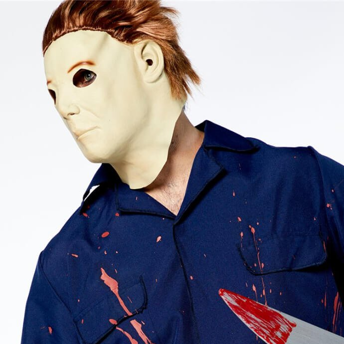 A man wearing a Michael Myers costume and mask holding a bloody fake knife