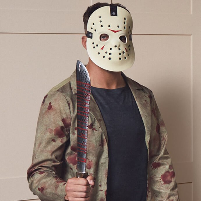 A man wearing a Jason Voorhees costume and mask holds a bloody machete menacingly