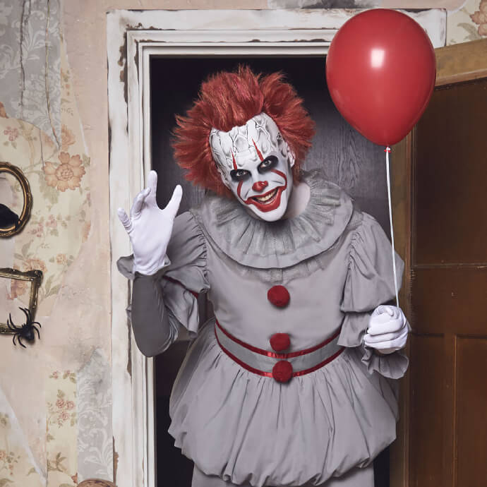 A modern version of Pennywise lurks in the doorway waving and holding a single red balloon