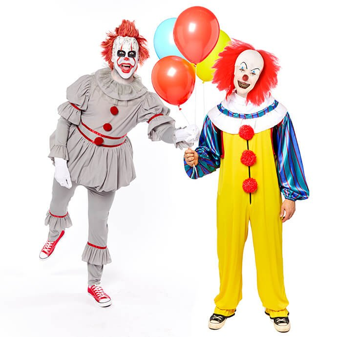A man in a modern Pennywise costume leans in to steal balloons from someone dressed as classic Tim Curry Pennywise