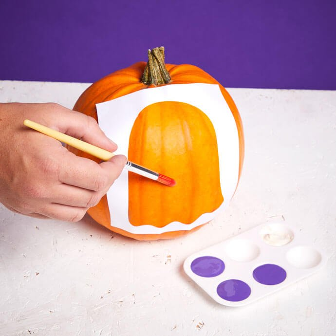 Pumpkin with stencil taped to it and brush starting to paint on purple acrylic paint