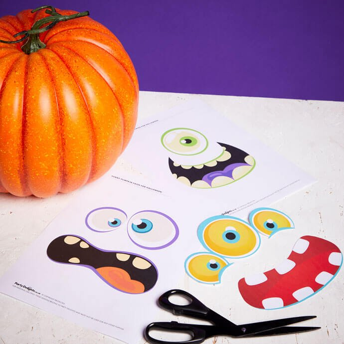 Printed out funny pumpkin faces on a table with a pair of scissors