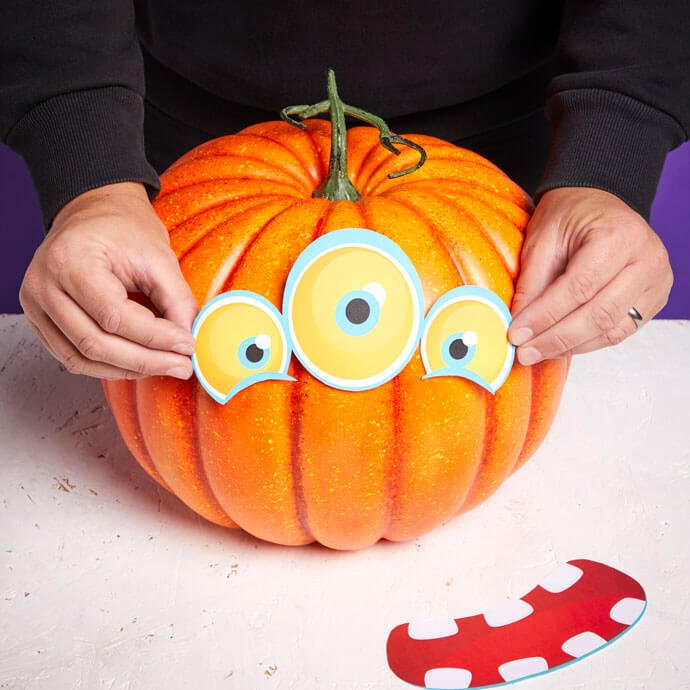 Hands positioning a pair of cut out eyes onto a pumpkin while the cut out face sits beside