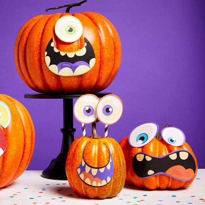 Pumpkins with funny faces, one of which has eyes on straw stalks