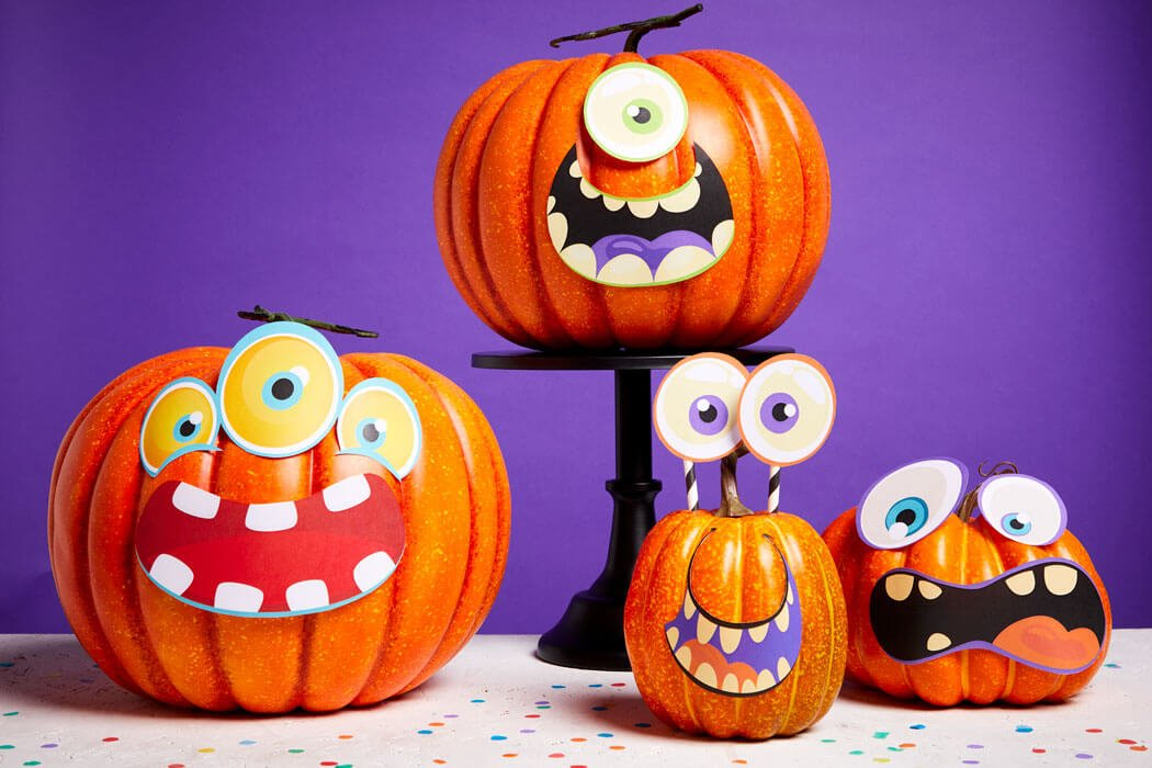 Four pumpkins lined up on a table with silly monster faces stuck on them