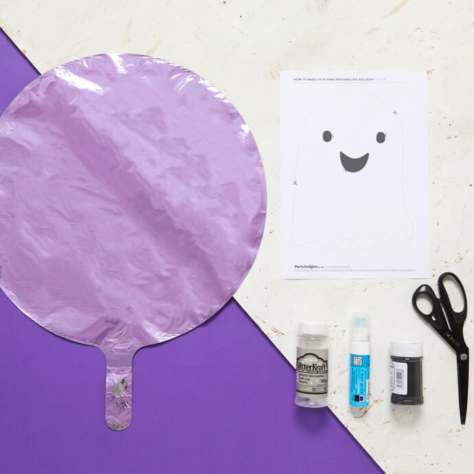 Purple balloon uninflated on a table with glue, glitter, scissors and a print-out