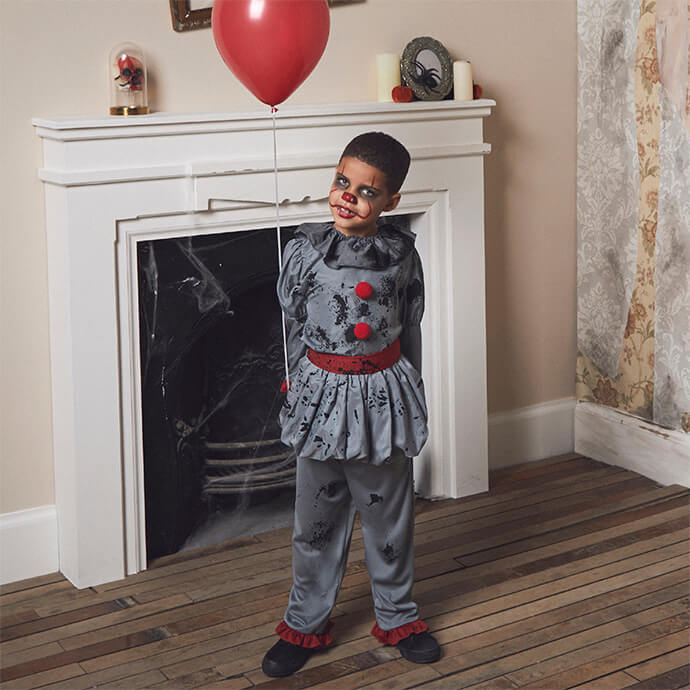 A young boy in a modern Pennywise costume holding a balloon in front of a fireplace