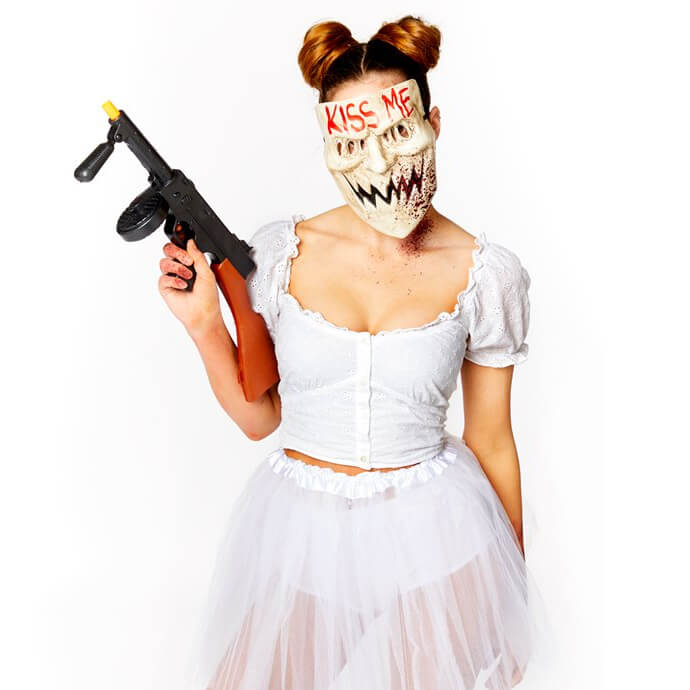 A woman dressed as Candy Girl from The Purge, wearing a white tutu, creepy mask and holding a fake gun